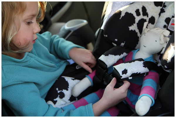 Preparing for baby: practicing strapping her baby doll into the infant car seat