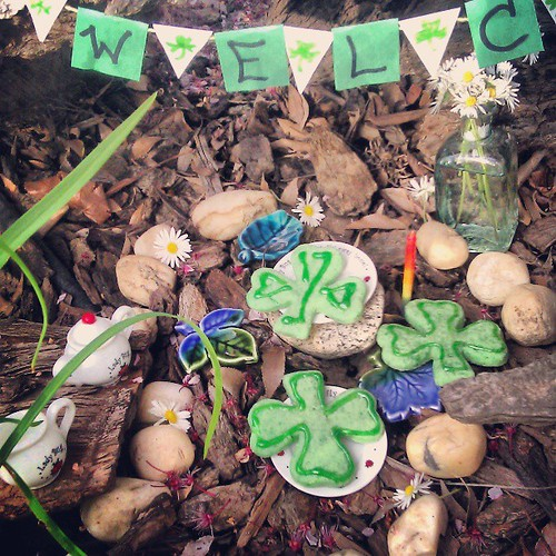 "Leprechaun party is all ready for the Wee Folk. We have shamrock cookies, milk, and honey for them. Asher brought some pretty flowers to make it beautiful, and we have a wee banner that says ""Welcome."""