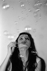Girl blowing bubbles at a birthday party by us&them.