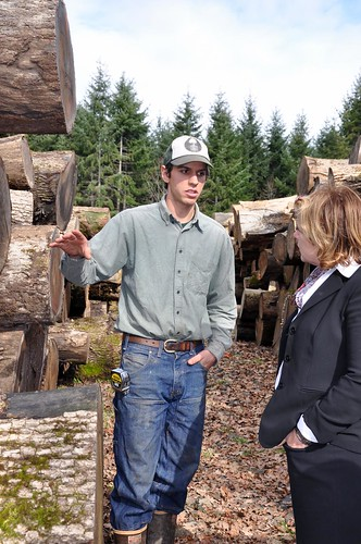 Ben Deumling (left) explains to USDA's Lillian Salerno the uses and values of different sizes of sustainably harvested Oregon white oak.