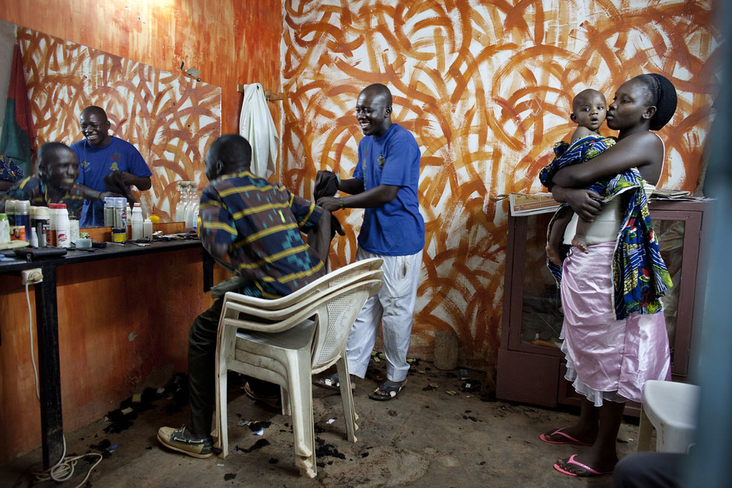 A barber finishes a haircut while his wife and child wait in Ouagadougou