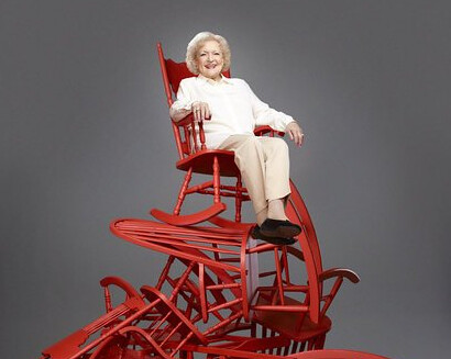 Betty White sitting on a pile of chairs