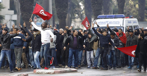 Protesters gesture to the police during a demonstration in Tunis February 6, 2013. Tunisian police fired teargas to disperse protesters demonstrating in the capital outside the Interior Ministry against the killing of a prominent opposition figure. by Pan-African News Wire File Photos