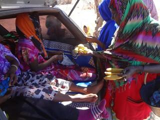 Mulheres na mala do táxi a comprarem fruta