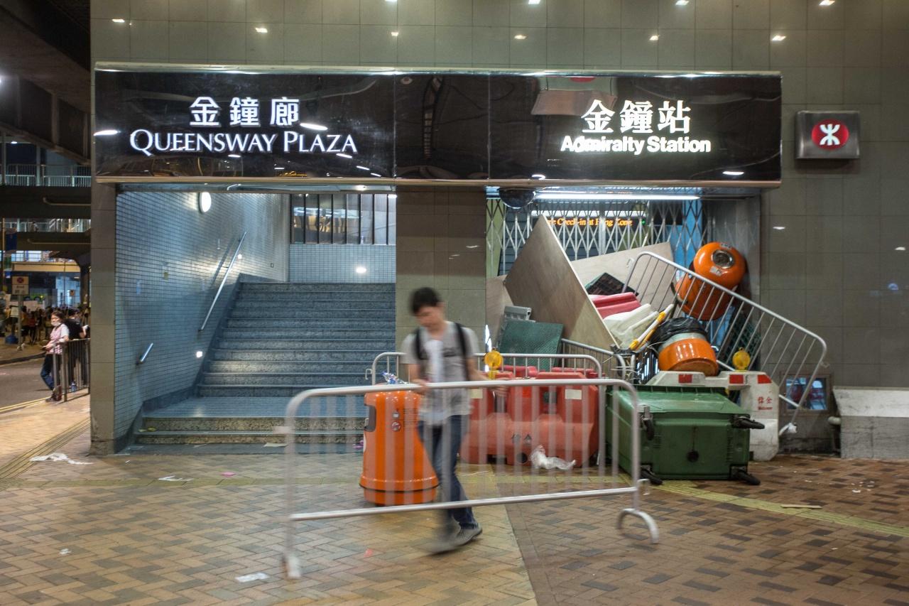 一位默默無名的年青示威者,把擋在金鐘港鐵站出口的障礙物逐一搬走。(相片由作者提供)