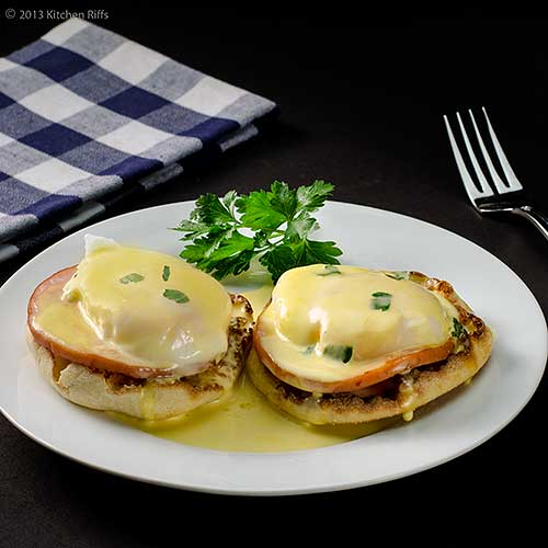 Eggs Benedict on plate with napkin and fork in background