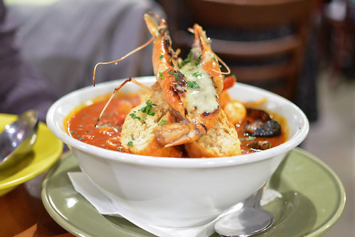 Cioppino Con Crostone All Aglio Traditional Italian fish soup with Manila Clams, Tiger shrimp, Black mussels and fish of the day topped with one Hawaiian jumbo fresh water prawn on garlic jumbo croutons