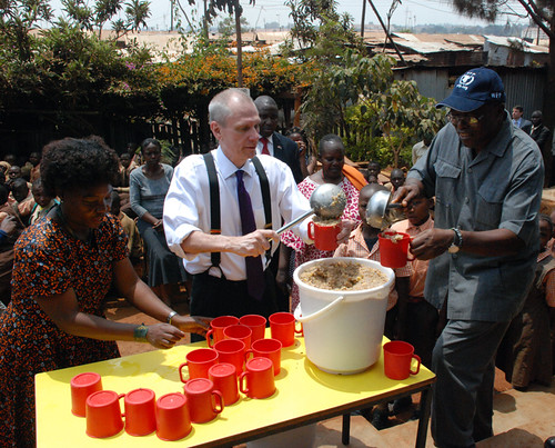 Ambassador Godec helps the Stara Rescue Center school founder and director, Josephine Mumo (left), and the World Food Program country director, Ronald Sibanda, prepare meals for the center's students. The center is just one of the beneficiaries of the USDA-funded program implemented by WFP in Kenya where U.S.-grown food feeds 650,000 children at more than 2,000 schools. (Courtesy Photo)