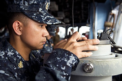 Senior Chief Electrician's Mate Wilbert Dispolo checks the distance of surface contacts using an alidade on the bridge of USS Tortuga (LSD 46) as the ship transits Manila harbor, April 2. (U.S. Navy photo by Mass Communication Specialist 3rd Class Amanda S. Kitchner)
