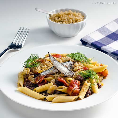 Pasta with Sardines and Fennel on white plate with napkin and fork in background