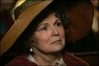Julie Walters as Mrs. Austen, wearing a giant hat