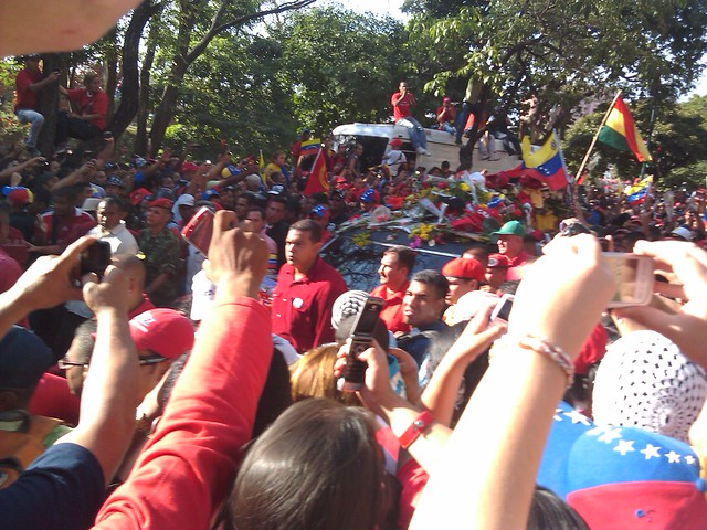Throngs of people straining to see and photograph Hugo Chavez's coffin as it traveled through the streets of Caracas.