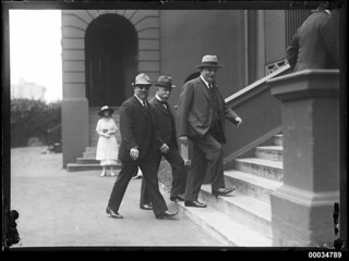 Three civilian officials ascending steps to Parliament House in Sydney