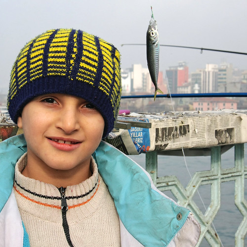A boy smiling with his fish on the Galata bridge, Istanbul, Turkey イスタンブール、ガラタ橋の少年