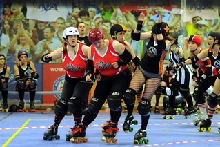 The Crucibelles jammer being pushed out of play by a pair of Whip-Its blockers