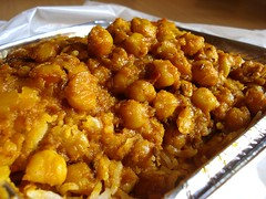A foil takeaway container piled high with a brownish-yellow chickpea curry. Grains of white rice are just visible beneath the curry.