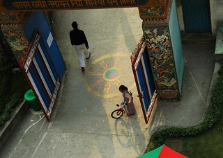A little Tibetan girl in the long shadows of the day with her bike, Dharma Wheel, front gate of Tharlam Monastery of Tibetan Buddhism, ornate carving, Boudha, Kathmandu, Nepal