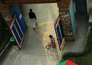 A little Tibetan girl in the long shadows of the day with her bike, Dharma Wheel, front gate of Tharlam Monastery of Tibetan Buddhism, ornate carving, Boudha, Kathmandu, Nepal