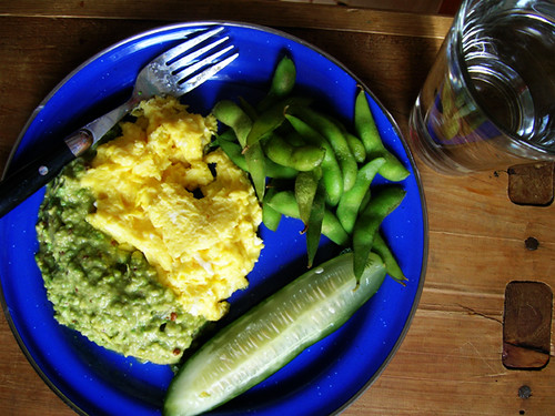 scrambled eggs and guacamole, edamame, pickle, and water