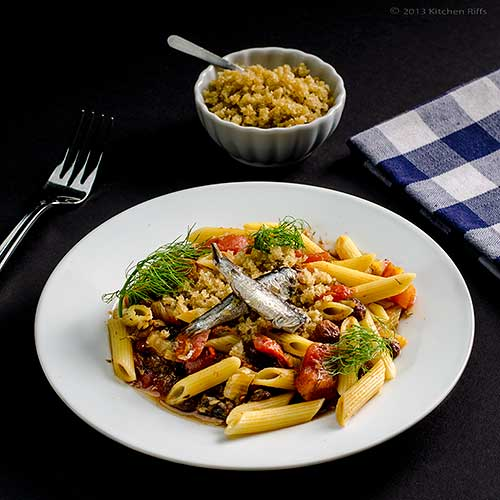 Pasta with Sardines and Fennel on white plate with napkin and fork in ...