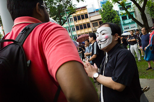 A guy in a Guy Fawkes mask speaking to his friend about the protest. The mask has come to symbolize protest, and was featured in the movie V for Vendetta.