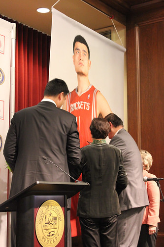 February 15th, 2013 - Yao Ming and his parents sign a poster of Yao in a Rockets uniform