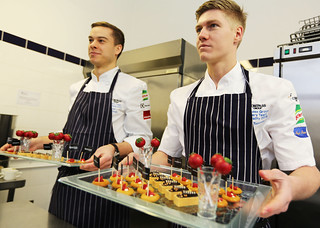 Two young men in chef aprons hold trays of canapes they've prepared.
