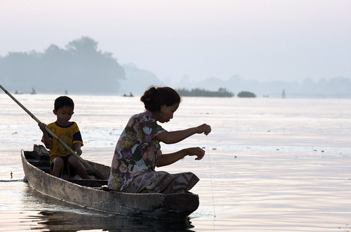 Fisherwoman checking a fishing line in Mekong, Laos. Photo by Patrick Dugan, 2009.