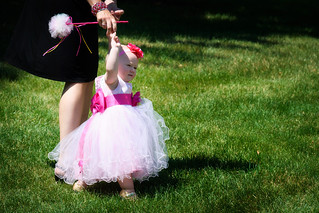 Toddler flower girl in a cute pink dress walking with her mother during a 2012 wedding
