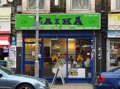 "A terraced shopfront with a sign above reading ""Zaika"" in dark text on a light green background. The shopfront is fully glazed with a glass door to the left and full-length windows. Stylised orange flame decals have been applied to the window, and a sign advertises chicken biryani for £2.99 (takeaway only)."