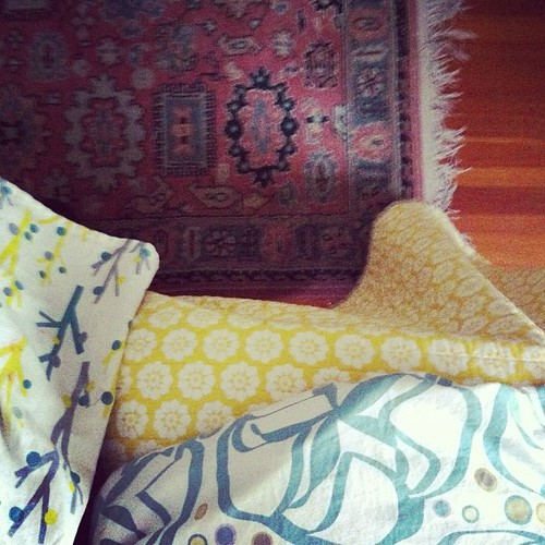 apron, rug, bed & blanket. a lot of patterns going on in one little spot.