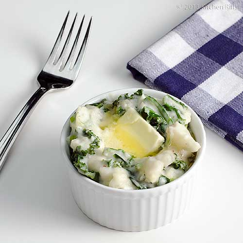 Colcannon in ramekin with butter garnish, fork and napkin in background