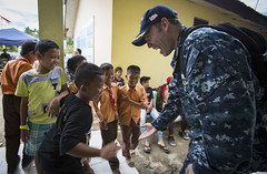 Cmdr. Miguel Gutierrez plays with Indonesian children during a Pacific Partnership 2016 surgical screening, Aug. 20. (USMC/Sgt. Brittney Vella)