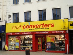 "A terraced shop stretching over two shopfronts. A sign above reads ""Cash Converters"" in red letters on a bright yellow background, with a light blue arrow circling the words. The frames of the large shop windows are also red, and above the windows the words ""we buy - we sell - we loan cash - cheques cashed - pawnbroking"" are printed in white letters. Various electronic goods are displayed in the windows."