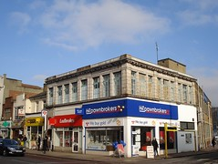 A corner building viewed on a bright day with just a few clouds in the blue sky. The aspect is square and the roof is flat. The upper floor has masonry detailing and metal-framed windows, while the lower floor has somewhat gaudy shopfronts for H&T Pawnbrokers on the corner (white lettering and red detailing on a dark blue background) and Ladbrokes next to it (white lettering on a red background). Other shopfronts stretch away to the left.