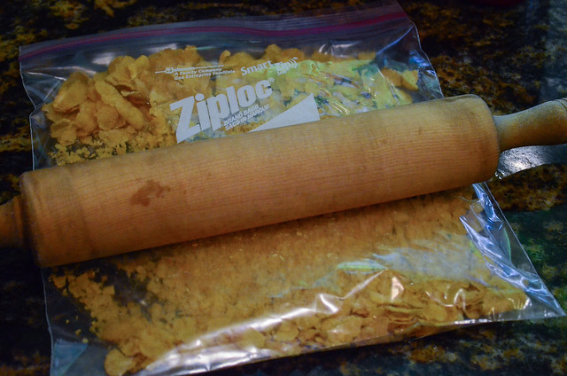 Corn flakes inside a Ziploc bag being crushed by a rolling pin.