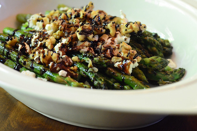 Roasted Asparagus with Balsamic, Goat Cheese & Toasted Walnuts in a serving dish.