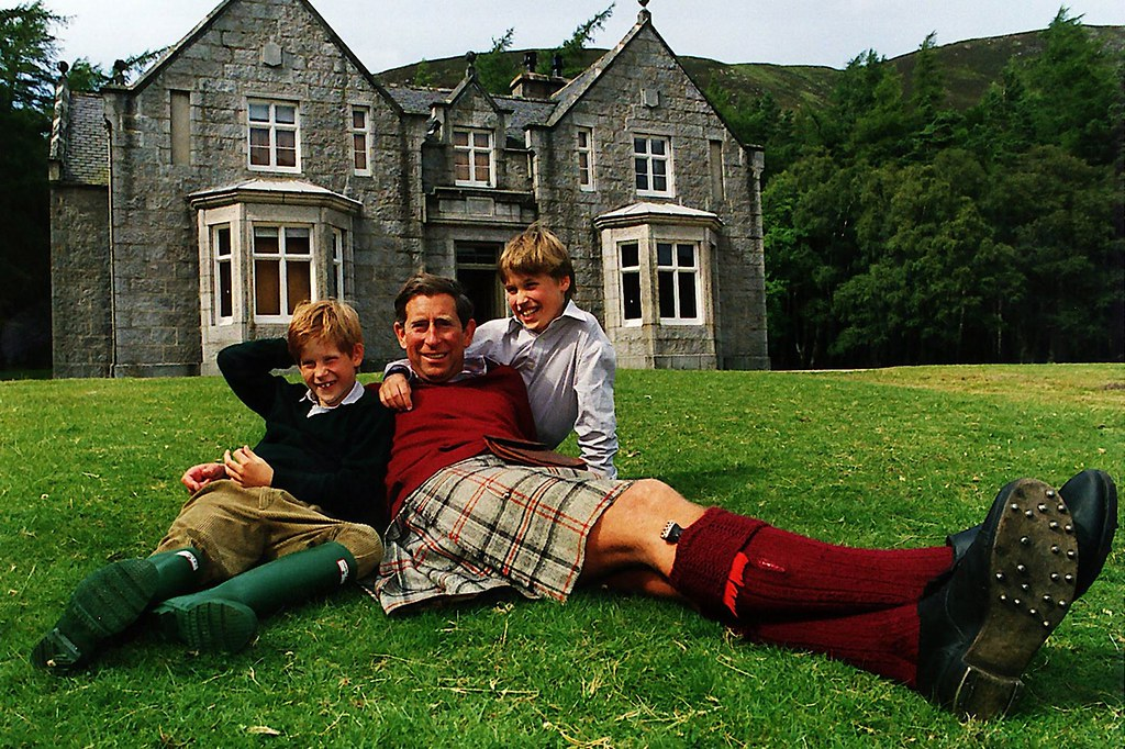 1990 Prince Charles with Prince Williaman Prince Harry lying on the grass outside a country house wearing Kilt and wellies in the 1990s