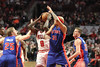 Chicago Bull Luol Deng goes up for a shot while guarded by Detroit Pistons Kyle Singler and Charlie Villanueva