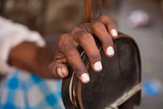 Hands of a man with a traditional instrument in Kolkata, India.