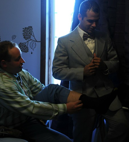 Groomsman Tyler Rohl putting on his socks, groom, Chris, getting dressed in gray three-piece suit, vintage attire, Wedding of Jessie and Chris, Fairbanks, Alaska, USA by Wonderlane