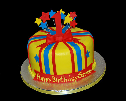 yellow blue and red first birthday cake