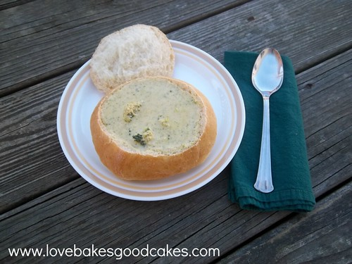 Broccoli and Cheese Soup in Homemade Bread Bowl on plate with spoon and napkin.