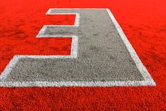 asphalt(0.0), number(0.0), lane(0.0), road surface(0.0), flooring(0.0), red(1.0), font(1.0), mat(1.0),