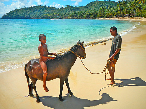 Dominican boy on horse with dad on beach