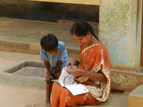 Teacher and student reading our books at Hosahudya govt. primary school, Ugadi gifts. - by zenrainman