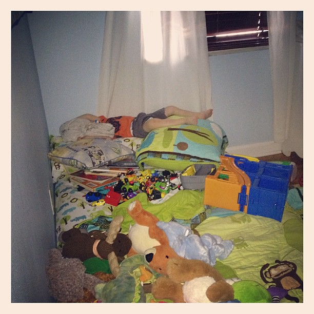 How my crazy boy is napping. He brought a pile of books, his car ramp, and all of his cars into bed w him. #seemslegit #toddlerlogic