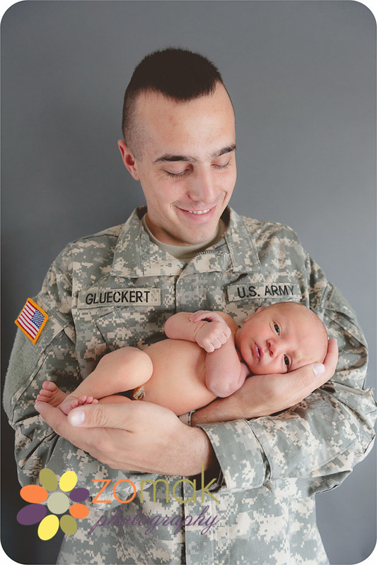 Best newborn photo being held in the arms of his dad who is wearing his army uniform