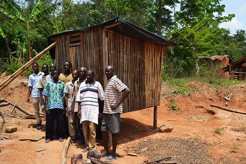 Farmers stand in front of a new chicken house.