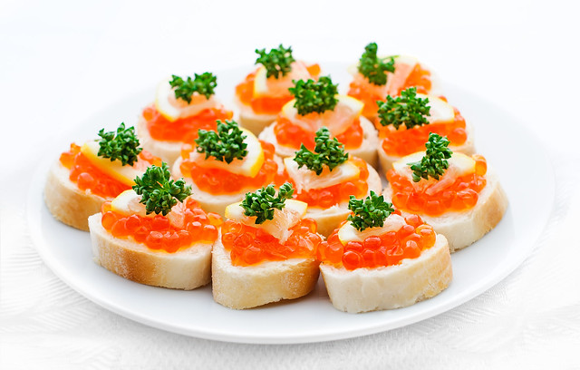 Canapes with salmon caviar, lemon and parsley